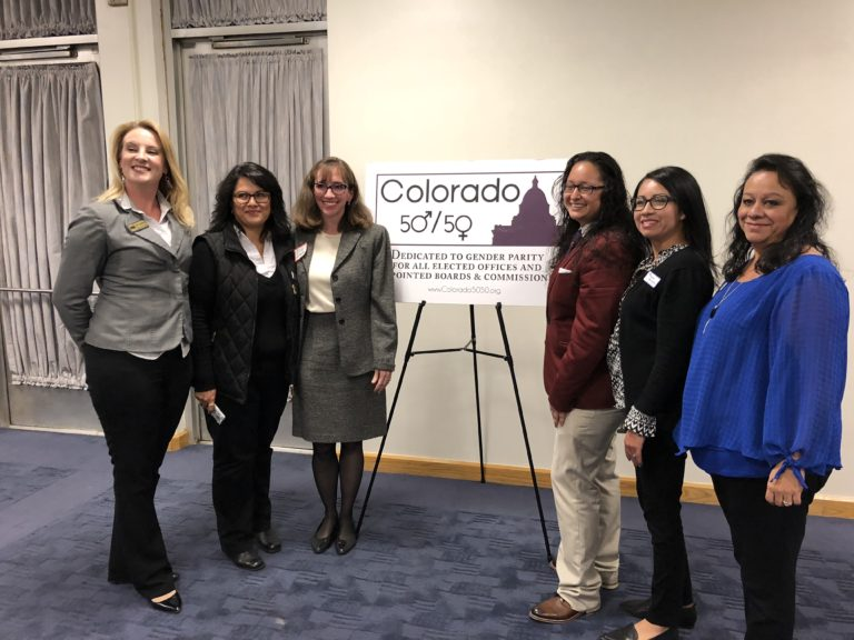 Six women with a Colorado 50-50 sign