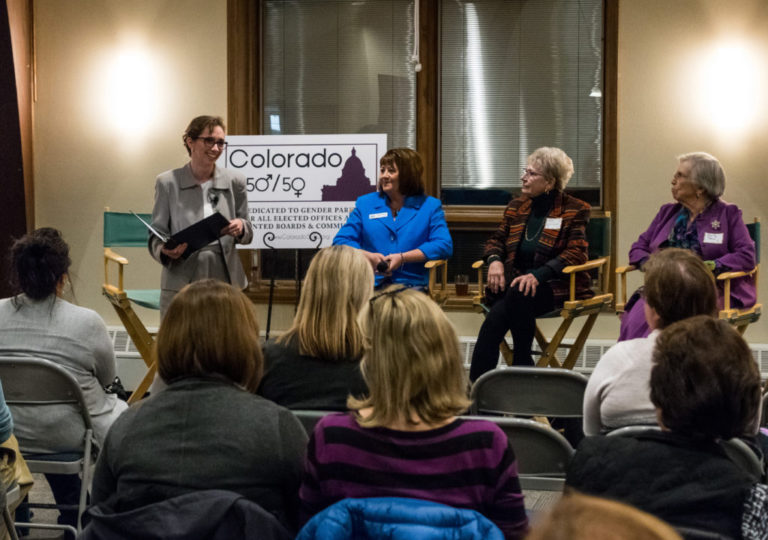 Four women speakers facing an audience
