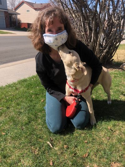 Woman wearing cloth mask and a puppy